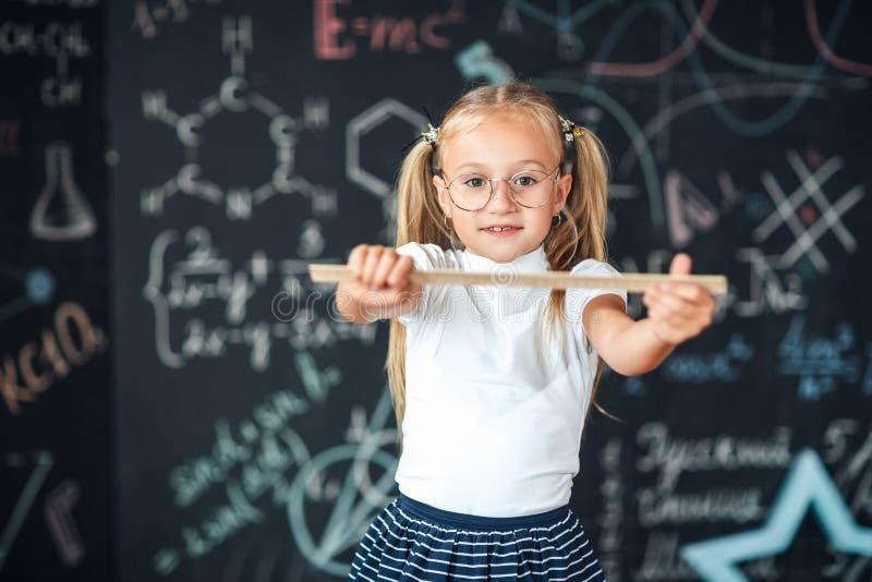 Урок математики Образование и знание Дисциплины школы СТЕРЖНЯ Девушка зрачка с большим правителем небольшая задняя часть девушки  стоковое изображение