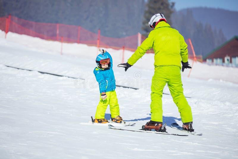 Урок на школе катания на лыжах: инструктор уча маленькому лыжнику стоковые фотографии rf