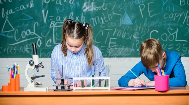 Урок химии школы Лаборатория школы Эксперимент по школы проведения студентов девушки и мальчика умный Опишите химическое стоковое фото