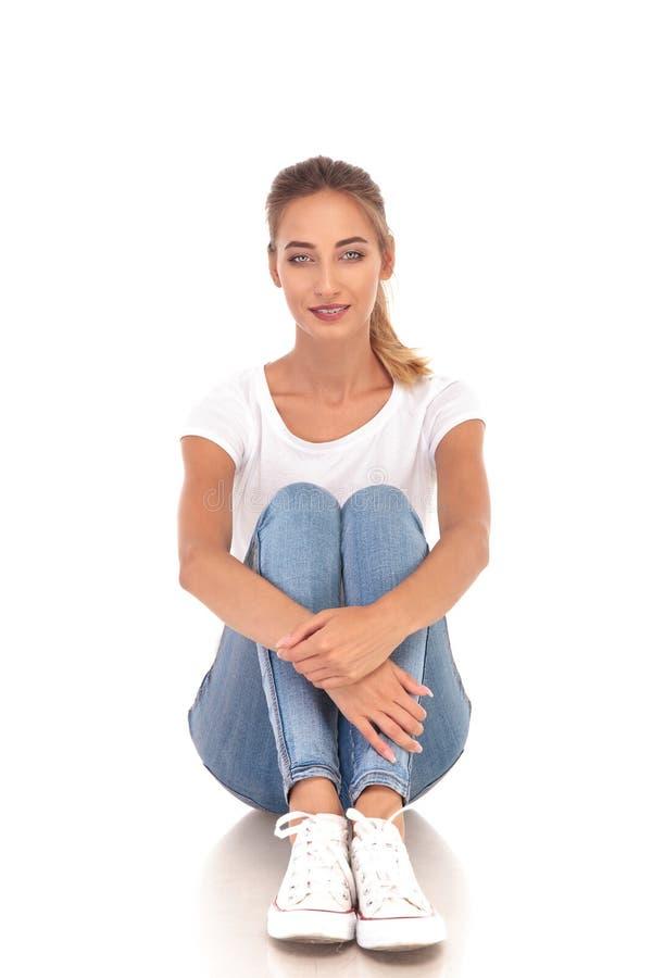 Усаженная вскользь женщина держа колени к ее комоду стоковая фотография