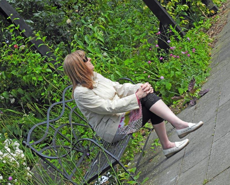 Усаженная женщина в розарии стоковые фотографии rf