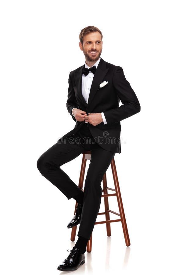 Усаженный бизнесмен застегивает костюм и смотрят, что встает на сторону стоковое фото