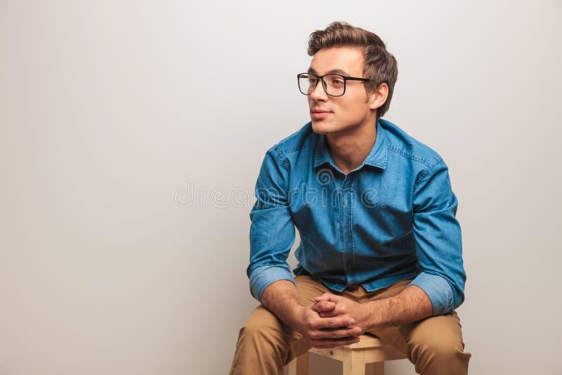 Усаженный молодой студент думает стоковое фото