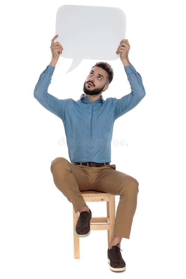Усаженный современный человек держа пустой знак сообщения пока смотрящ вверх стоковое фото rf