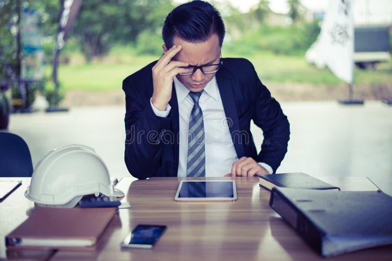 Усаживание бизнесмена и его сжиманная рукой голова, он чувствовать усиленный и тоскливость, стоковые изображения rf