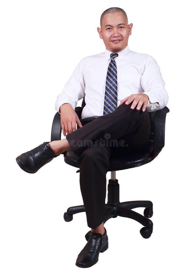 Усаживание бизнесмена на стуле изолированном на белизне стоковое фото