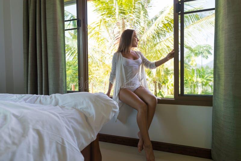 Усаживание женщины бодрствующее на силле окна наслаждается тропической спальней взгляда леса стоковые изображения rf