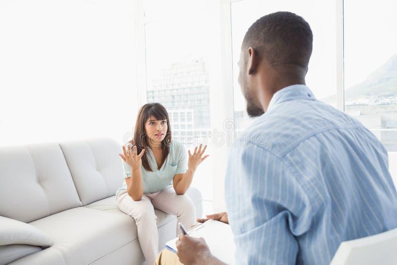 Усаживание женщины пока терапевт смотря ее стоковая фотография rf