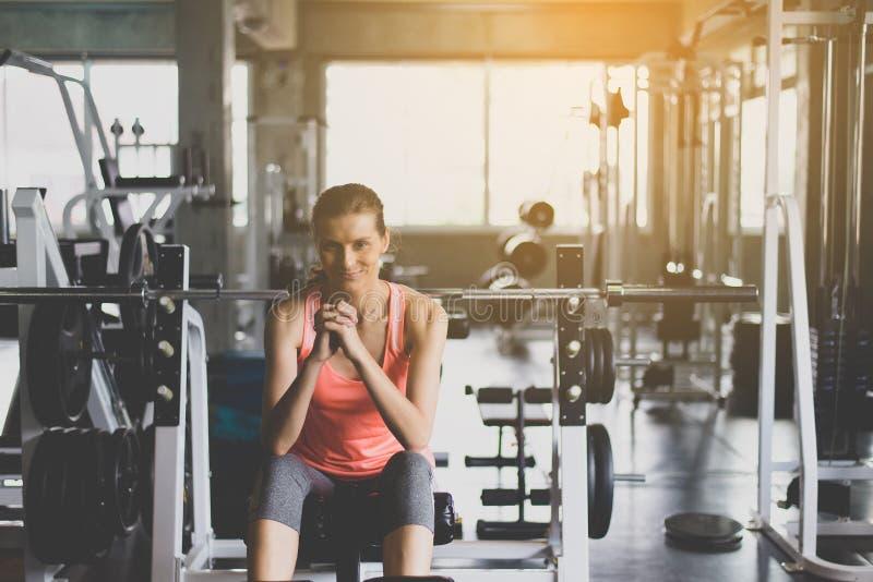 Усаживание женщины пригонки и ослабить после встречи в спортзале, концепции здоровой и образа жизни, женского принимающ перерыв п стоковые изображения rf