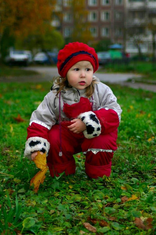 усаживание зеленого цвета травы девушки стоковое изображение