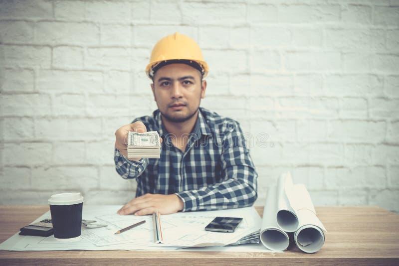Усаживание инженера или архитектора, деятельность на его столе в офисе стоковое фото rf