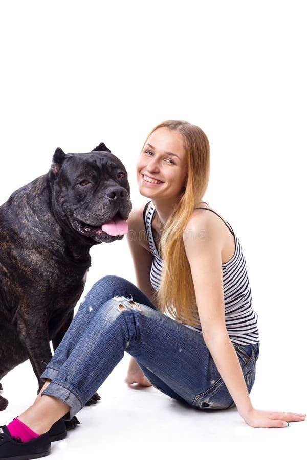 Усаживание и улыбка девушки рядом с его тросточкой Corso собаки стоковые фотографии rf