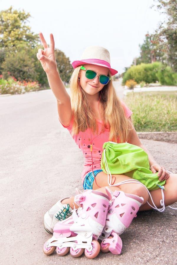 Усаживание кататься на коньках ролика предназначенное для подростков (девушка) с ботинками кататься на коньках ролика стоковые фотографии rf
