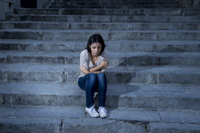 Усаживание красивой и унылой испанской женщины отчаянное и подавленное на городской лестнице улицы города стоковые изображения