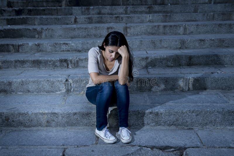 Усаживание красивой и унылой испанской женщины отчаянное и подавленное на городской лестнице улицы города стоковые фото