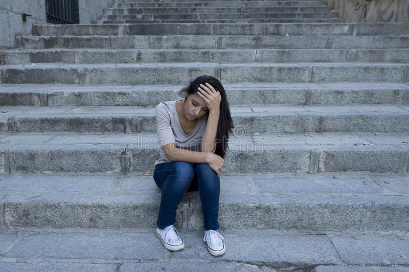 Усаживание красивой и унылой испанской женщины отчаянное и подавленное на городской лестнице улицы города стоковое изображение