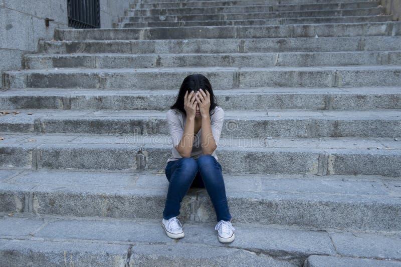 Усаживание красивой и унылой испанской женщины отчаянное и подавленное на городской лестнице улицы города стоковое изображение rf