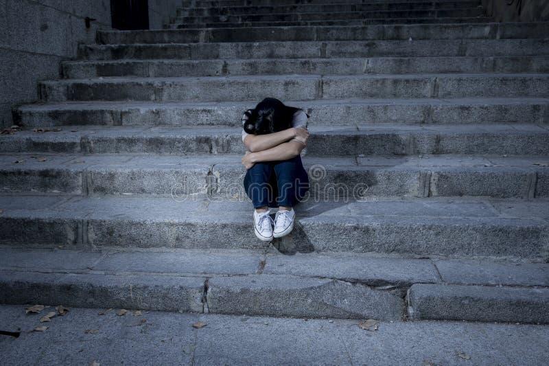 Усаживание красивой и унылой испанской женщины отчаянное и подавленное на городской лестнице улицы города стоковая фотография rf
