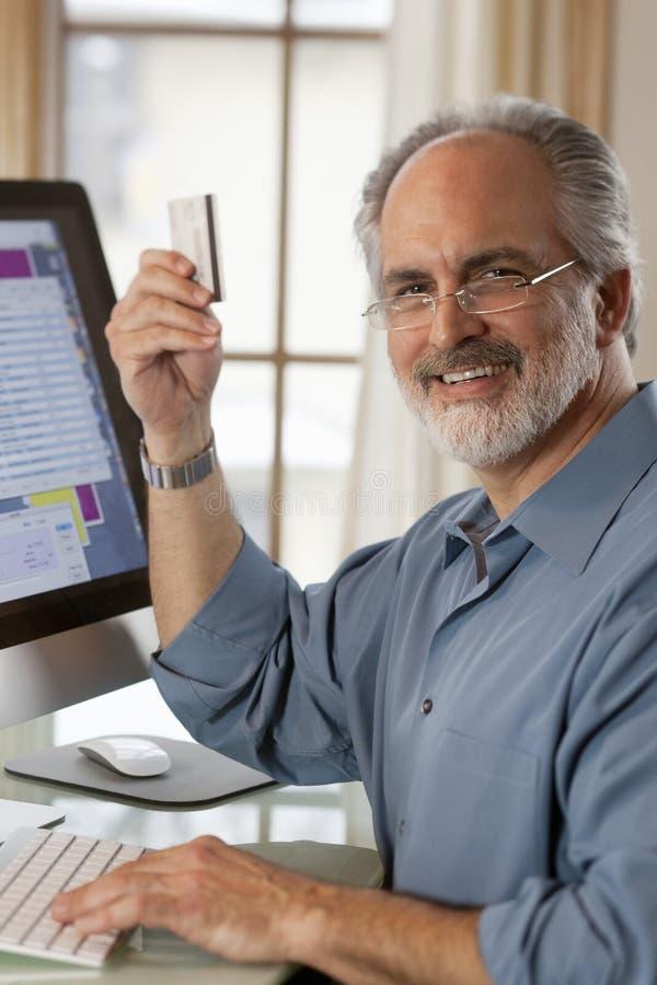 усаживание кредита компьютера карточки бизнесмена стоковые изображения