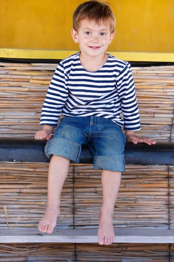 усаживание мальчика пляжа штанги счастливое стоковое изображение rf