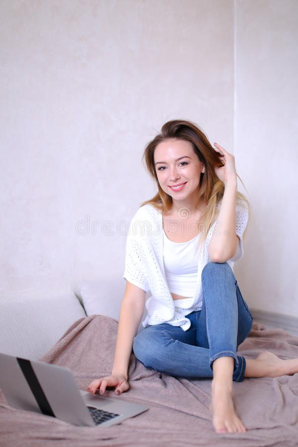 Усаживание молодой женщины и компьтер-книжка использования на кровати стоковое изображение