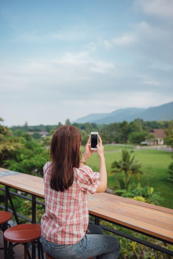 Усаживание путешественника молодой дамы и ослаблять в тайском ресторане принимая фото с умным телефоном на гору стоковая фотография