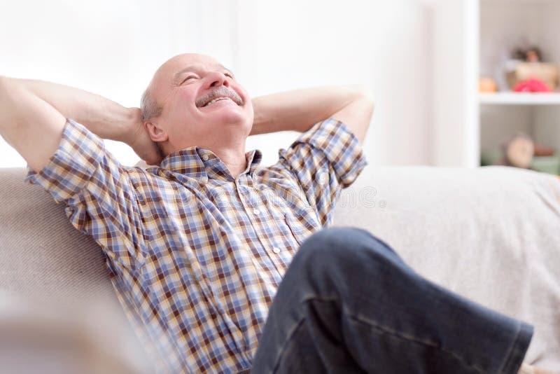 Усаживание счастливого привлекательного старшего человека отдыхая и дыша на кресле дома стоковое фото