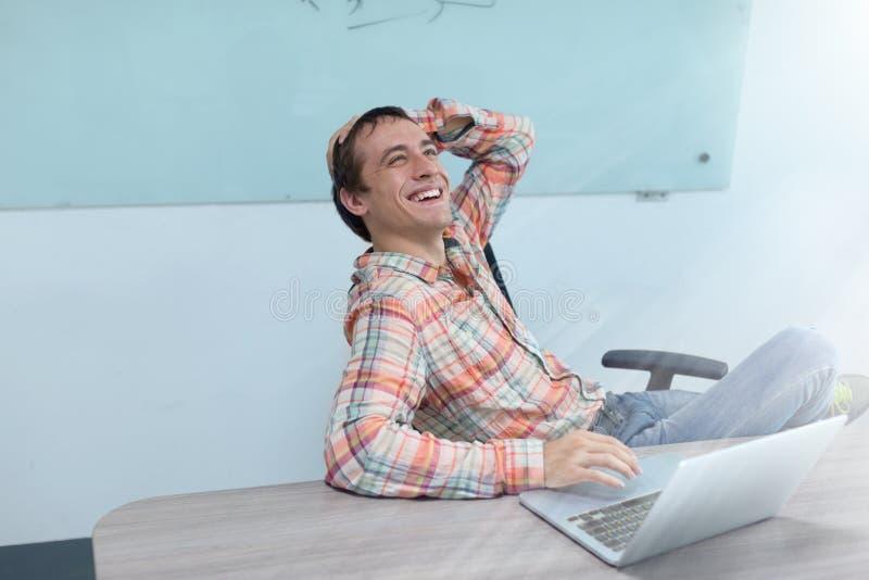 Усаживание улыбки excited бизнесмена успеха счастливое стоковое изображение