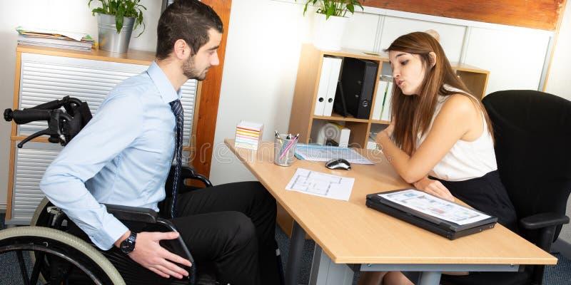 Усаживание человека в деятельности кресло-коляскы в современном офисе имея обсуждение с женским коллегой стоковое фото rf
