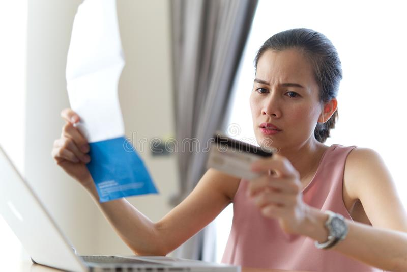 Усиленная азиатская женщина держа кредитную карточку и счеты чувствуя беспокойство об ее задолженности стоковая фотография rf