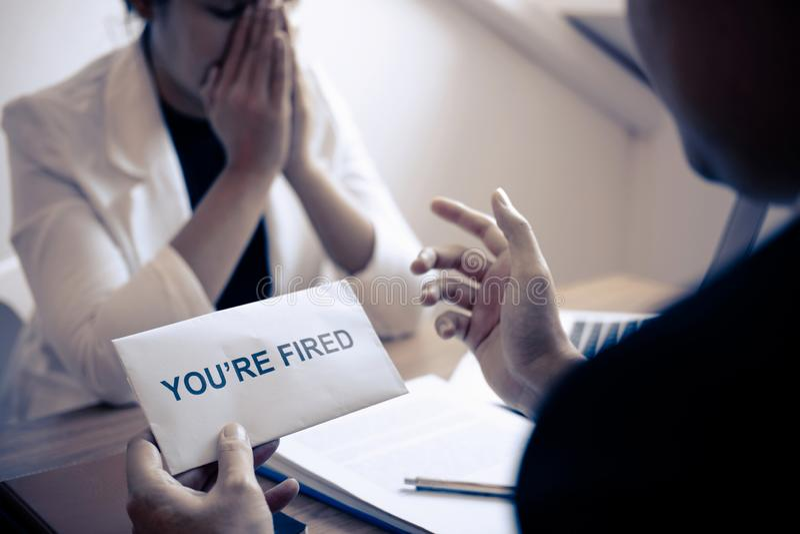 Усиленная бизнес-леди получает увольнятьое письмо от работодателя и пакуя пожитков и файлы в коричневую картонную коробку, изменя стоковое фото rf
