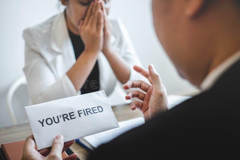 Усиленная бизнес-леди получает увольнятьое письмо от работодателя и пакуя пожитков и файлы в коричневую картонную коробку, изменя стоковое фото