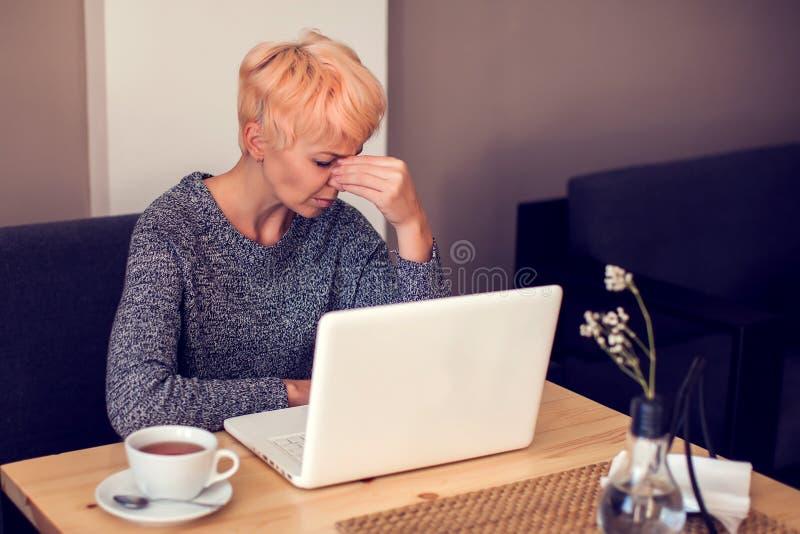 Усиленная женщина работая с головной болью чувства ноутбука стоковое фото