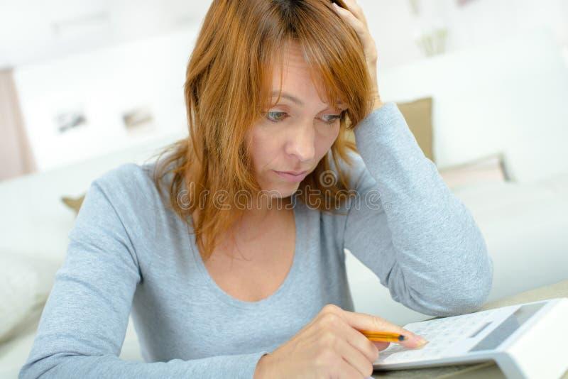 Усиленная женщина смотря на финансовые затруднения стоковая фотография