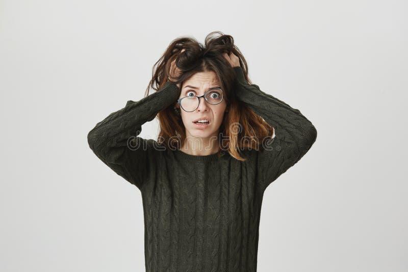 Усиленная тревоженая молодая женщина в вскользь одеждах, нося зрелищах, срывая волосах из-за стресса пока смотрящ на проблемы стоковые изображения rf