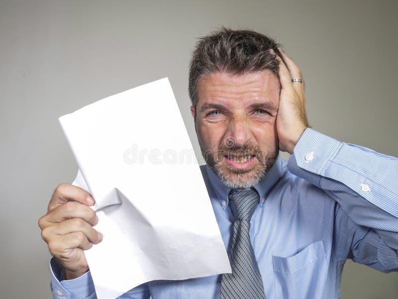 Усиленное и сокрушанное 30s к бизнесмену 40s в рубашке и галстуке усилило и сокрушало с бумагой в его осадке чувства руки стоковое изображение