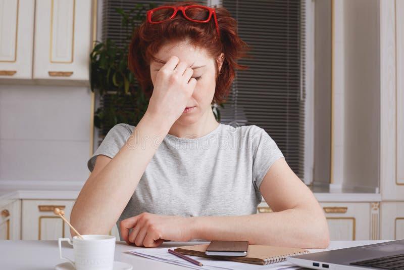 Усиленные быть усталости молодые женские перегружанными попытками, который нужно сконцентрировать, окруженный с бумагами и соврем стоковая фотография rf
