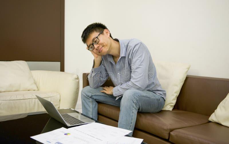 Усиленный азиатский бизнесмен используя smartphone в живущей комнате на стоковое изображение
