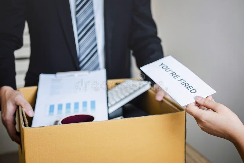 Усиленный бизнесмен получает увольнятьое письмо от работодателя и пакуя пожитков и файлы в коричневую картонную коробку, изменяя  стоковое изображение rf