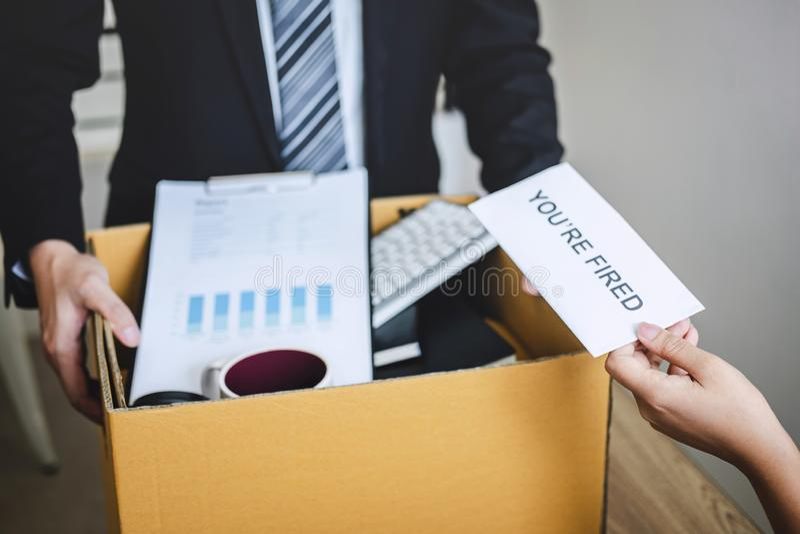 Усиленный бизнесмен получает увольнятьое письмо от работодателя и пакуя пожитков и файлы в коричневую картонную коробку, изменяя  стоковые изображения rf