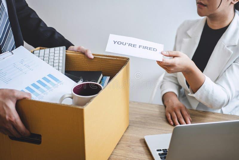 Усиленный бизнесмен получает увольнятьое письмо от работодателя и пакуя пожитков и файлы в коричневую картонную коробку, изменяя  стоковые изображения