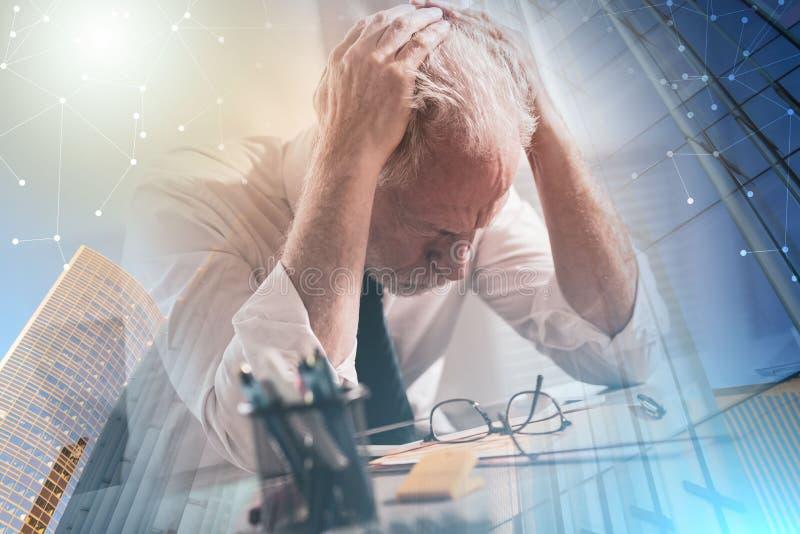Усиленный бизнесмен сидя в офисе; множественная выдержка стоковые фото