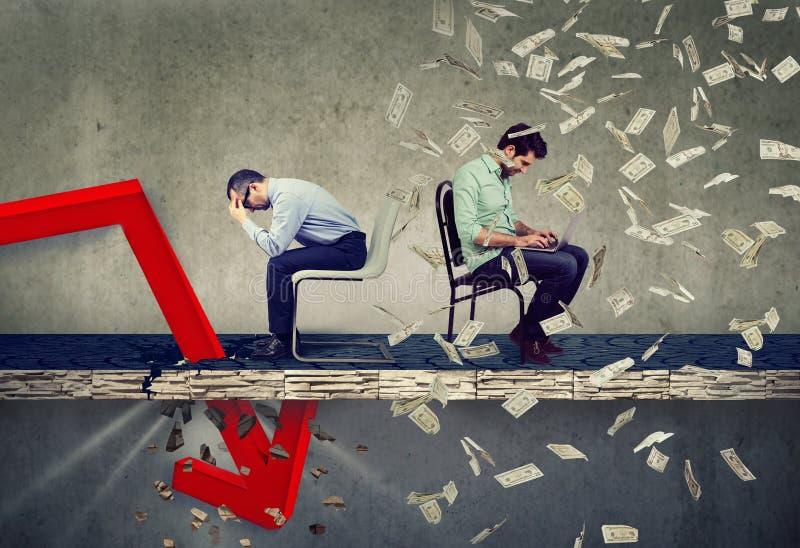 Усиленный бизнесмен смотря вниз на падать вниз стрелка сидя рядом с успешным парнем работая на ноутбуке под дождем денег стоковые изображения