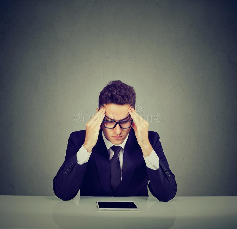 Усиленный молодой бизнесмен сидя на столе с планшетом стоковые фотографии rf