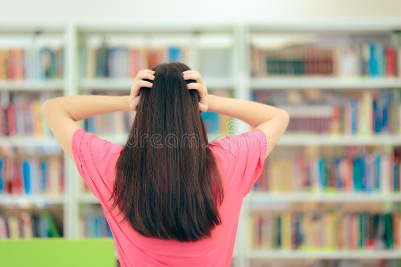 Усиленный студент подготавливая для экзаменов в школьной библиотеке стоковое изображение