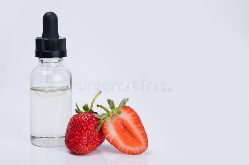 Усиливающий агент ароматности и вкуса рядом с зрелыми клубниками, на белой предпосылке стоковое изображение