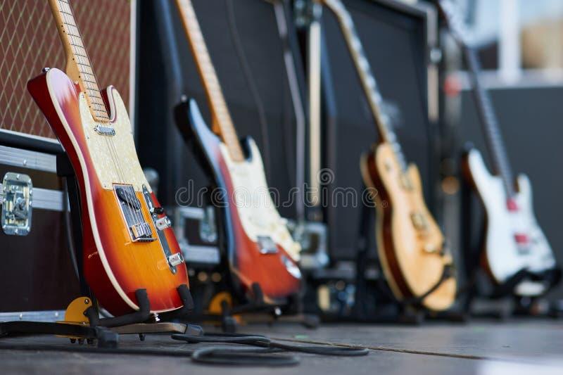 Усилитель с электрической гитарой на этапе аппаратура музыки установленная для гитариста отсутствие людей стоковое фото