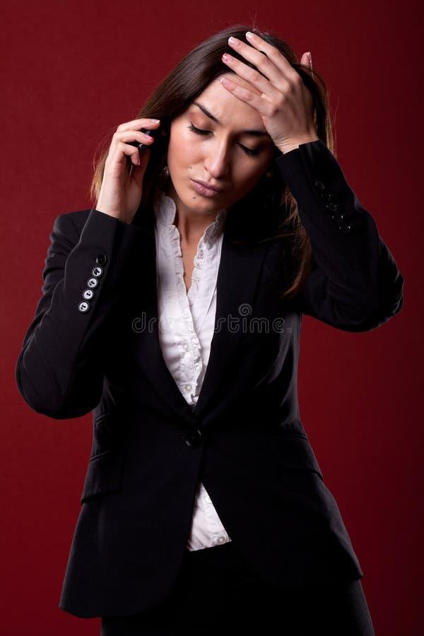 Усиленная бизнес-леди имея головную боль над белизной стоковое фото rf