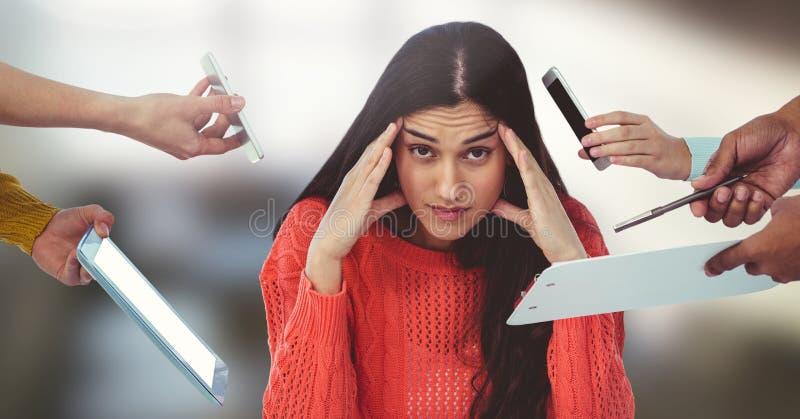 Усиленная женщина окруженная телефонами и файлами и таблеткой в офисе стоковые изображения rf