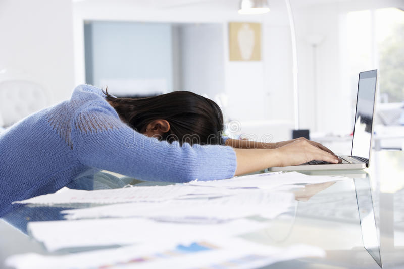 Усиленная женщина работая на компьтер-книжке в домашнем офисе стоковые фото